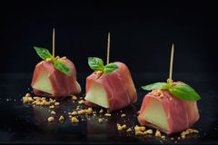 Prosciutto e melone. Small portions of melon wrapped in prosciutto, presented with basil leaves and peanut crumb on a black background Stock Photography
