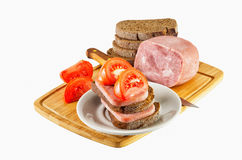 Prosciutto e pomodori che si trovano sul piatto e sui precedenti isolati Fotografie Stock Libere da Diritti