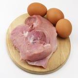 Prosciutto ed uova crudi della carne di maiale sul tagliere di legno su backgroun bianco Immagini Stock Libere da Diritti