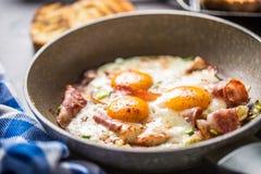 Prosciutto ed uova fritti del bacon della prima colazione inglese in pentola ceramica immagini stock