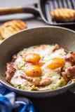 Prosciutto ed uova fritti del bacon della prima colazione inglese in pentola ceramica fotografia stock libera da diritti