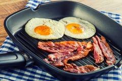 Prosciutto ed uovo Bacon ed uovo Uovo salato e spruzzato con pepe nero Bacon arrostito, due uova in una pentola del teflon immagini stock libere da diritti