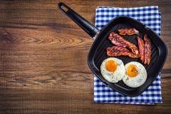 Prosciutto ed uovo Bacon ed uovo Uovo salato e spruzzato con pepe nero Bacon arrostito, due uova in una pentola del teflon immagini stock