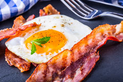 Prosciutto ed uovo Bacon ed uovo Uovo salato e spruzzato con pepe nero e la decorazione verde dell'erba Fotografie Stock Libere da Diritti