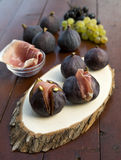 Prosciutto with fresh figs. Italian ham with fresh figs on wooden platter Stock Photography