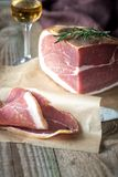 Prosciutto with fresh rosemary on the wooden board. Close up Stock Image