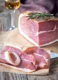 Prosciutto with fresh rosemary on the wooden board. Close up Royalty Free Stock Photos