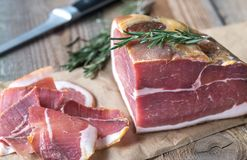 Prosciutto with fresh rosemary on the wooden board Royalty Free Stock Photo