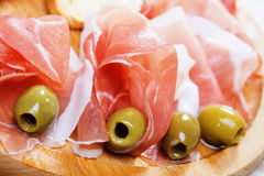 Prosciutto with green olives stock image