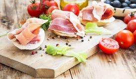 Prosciutto Ham Appetizer com especiarias em uma placa de corte de madeira Foto de Stock Royalty Free