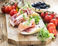 Prosciutto Ham Appetizer con las especias en una tabla de cortar de madera Fotos de archivo
