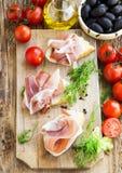 Prosciutto Ham Appetizer mit Gewürzen auf einem hölzernen Schneidebrett Lizenzfreie Stockbilder