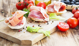 Prosciutto Ham Appetizer mit Gewürzen auf einem hölzernen Schneidebrett Lizenzfreies Stockfoto