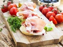 Prosciutto Ham Appetizer mit Gewürzen auf einem hölzernen Schneidebrett Stockbild