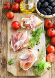 Prosciutto Ham Appetizer with Spices on a Wooden Cutting Board Royalty Free Stock Images