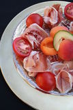 Prosciutto ham, apricots, tomato and cucumber. Plate with ham, fruit and vegetables Stock Photo