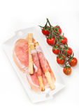 Prosciutto ham with bread sticks and cherry tomatoes Royalty Free Stock Photos