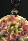 Prosciutto ham and Cantalope melon. Appetizer with Prosciutto ham and Cantalope melon together with a glass of red wine Royalty Free Stock Photo