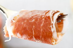 Prosciutto ham on fork Royalty Free Stock Image