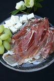 Prosciutto ham, fromage and grapes. Glass plate with appetizer of Prosciutto ham, grapes and fromage Royalty Free Stock Photo