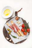Prosciutto ham grisiini breadsticks with olive oil and tomatoes Stock Photos