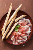 Prosciutto ham and grissini bread sticks. italian antipasto Royalty Free Stock Photo