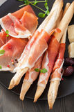 Prosciutto ham and grissini bread sticks. italian antipasto Royalty Free Stock Images