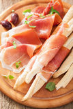 Prosciutto ham and grissini bread sticks. italian antipasto Stock Photography
