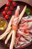 Prosciutto ham and grissini bread sticks. italian antipasto Stock Image
