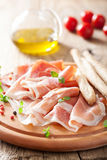 Prosciutto ham and grissini bread sticks. italian antipasto Royalty Free Stock Photos