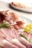 Prosciutto and ham plate. Delicious prosciutto and ham plate with rosemary and grapes Royalty Free Stock Image