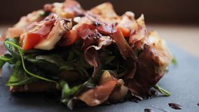 Prosciutto ham salad on stone plate at restaurant stock video