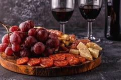 Prosciutto korv, vin, druva, parmesan på den mörka tabellen royaltyfria bilder