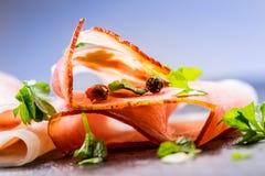 prosciutto Le fette arricciate di prosciutto di Parma delizioso con prezzemolo va sul bordo del granito Prosciuto con il garli de Immagine Stock