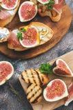 Prosciutto med fikonträd Nya fikonträd med skinka och ost på ett grillat rostat bröd, lantlig bakgrund aptitretande mellanmål Bäs arkivfoto