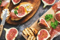 Prosciutto med fikonträd Nya fikonträd med skinka och ost på ett grillat rostat bröd, lantlig bakgrund aptitretande mellanmål Bäs royaltyfri bild
