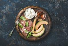 Prosciutto, melão do cantalupo, manjericão, mussarela e vidro do vinho cor-de-rosa Imagem de Stock