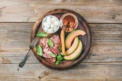 Prosciutto, melão do cantalupo, manjericão verde, mussarela e vidro do vinho Fotografia de Stock