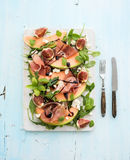 Prosciutto, melon, fig and soft cheese salad on a Stock Images