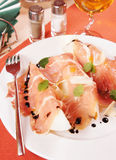 Prosciutto with melon on a laid table Stock Photo