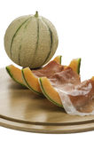 Prosciutto and melon and melon slices. Photographed on wooden plate Stock Photos