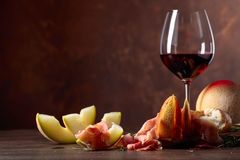 Prosciutto with melon and rosemary on a old wooden table. Glass of red wine and prosciutto with melon and rosemary on a brown background, copy space stock photo