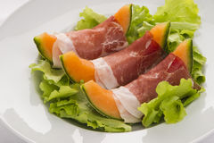 Prosciutto with melon on the salad leaf. Prosciutto with melon 3 slices on salad leafs in the white plate Royalty Free Stock Photos