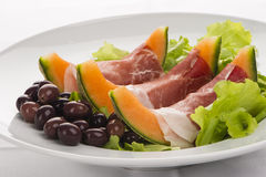 Prosciutto, melon, salad leaf and olives. From the side Royalty Free Stock Image