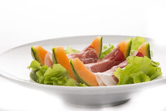 Prosciutto, melon, salad leaf on the white plate. From the side Stock Images