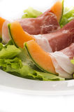 Prosciutto, melon and salad macro. Prosciutto with melon 3 slices with salad leafs Royalty Free Stock Photo