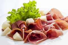 Prosciutto with melon on a white plate stock image