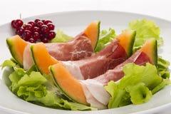 Prosciutto, Melone, Salatblatt und Korinthen Stockbilder