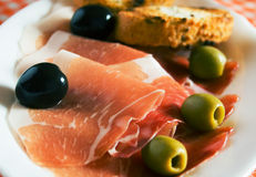 Prosciutto and olives Stock Photos