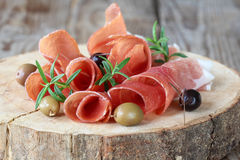 Prosciutto with olives and rosemary Stock Photo